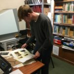 Our Young Curator Harvey choosing the photos for the 'Then and Now' display of historic photographs.