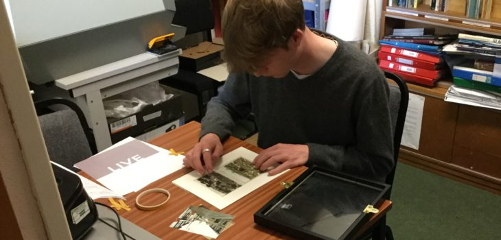 Harvey our Young Curator mounting the historic photographs from our collection.